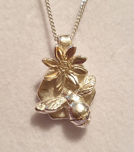 Silver bee on hexagon with flower