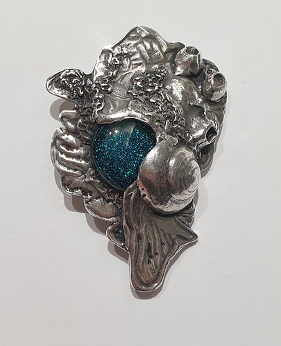 Large silver brooch depicting sea life around a blue cabochon