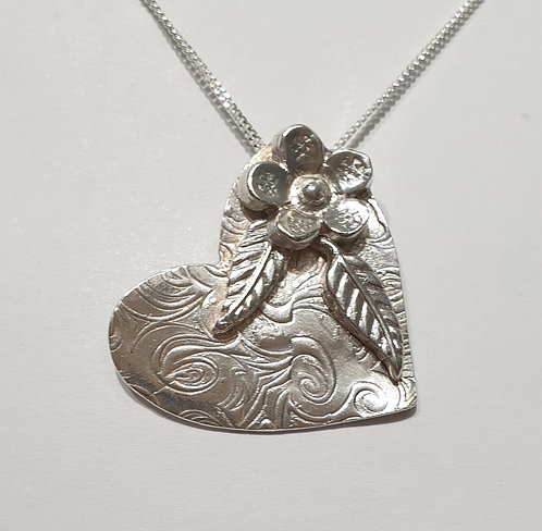 Silver heart with swirl pattern, flower and leaves at top