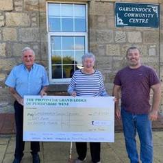 PG S Chaplain Duncan Kinloch and Lodge 1036  Treasurer Mark Kane present £100 to Ann Muirh