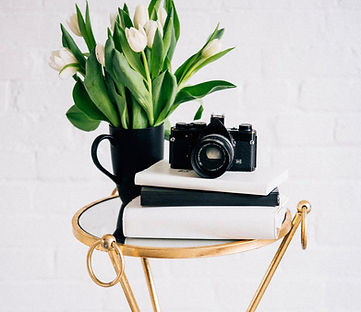 Photography camera on a side table with fresh lilies