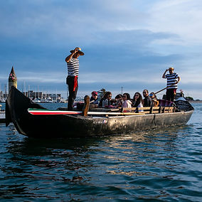 Gondolier takes guests in a group cruise through the enchanting Naples canals at Gondola Getaway on Belmont Shore