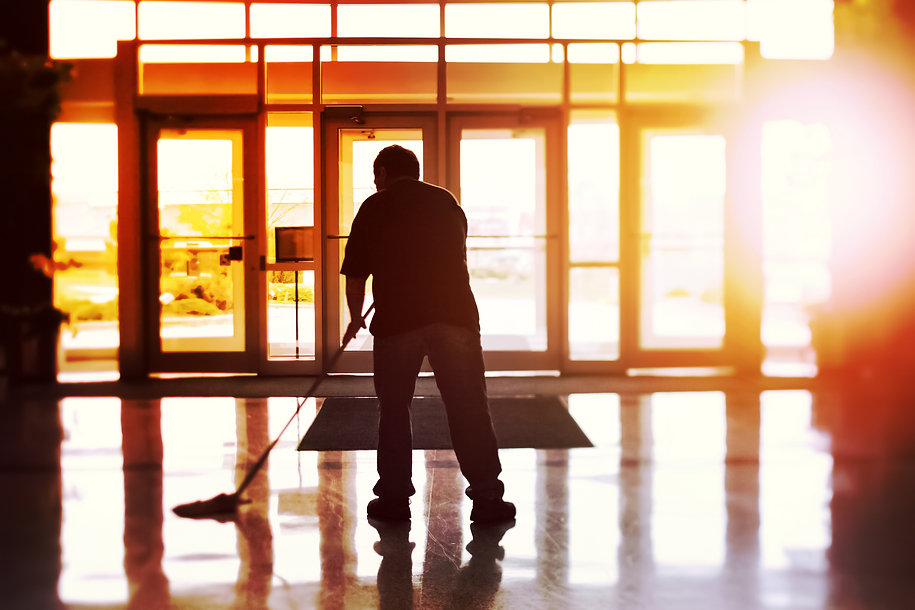 Janitor mopping an office floor, shallow focus, tilt shift image