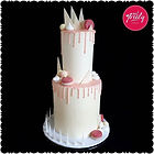 Pink and white chocolate drip cake topped with macarons, meringues, lindt ball and chocolate shards