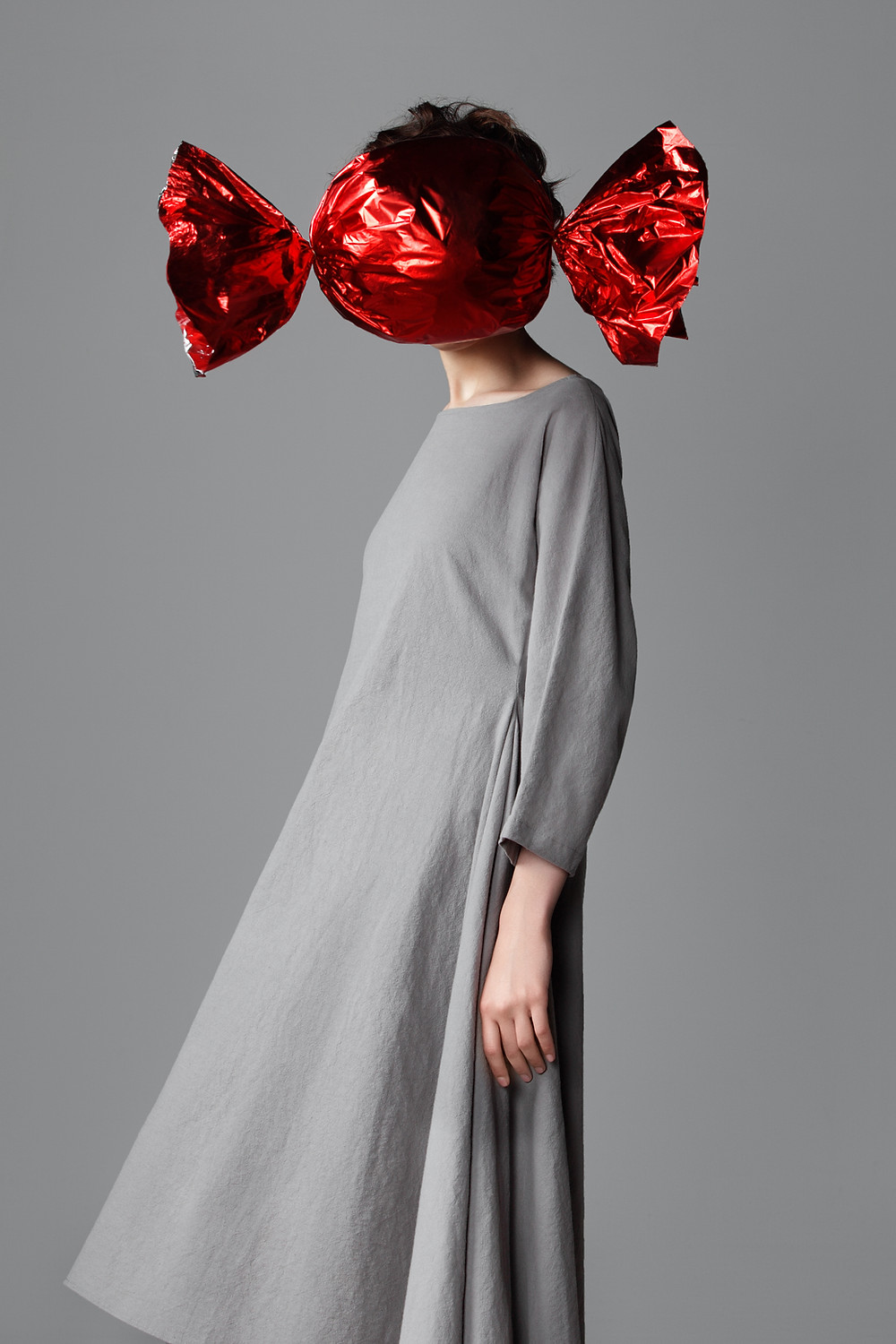 avante garde fashion art image of girl in grey dress with red candy head
