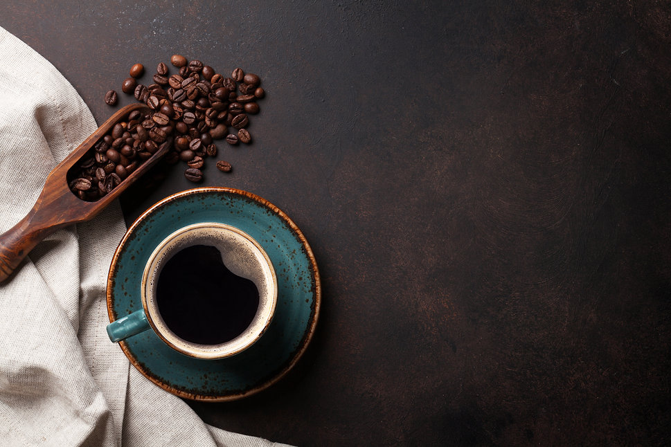 Coffee cup and beans on old kitchen tabl