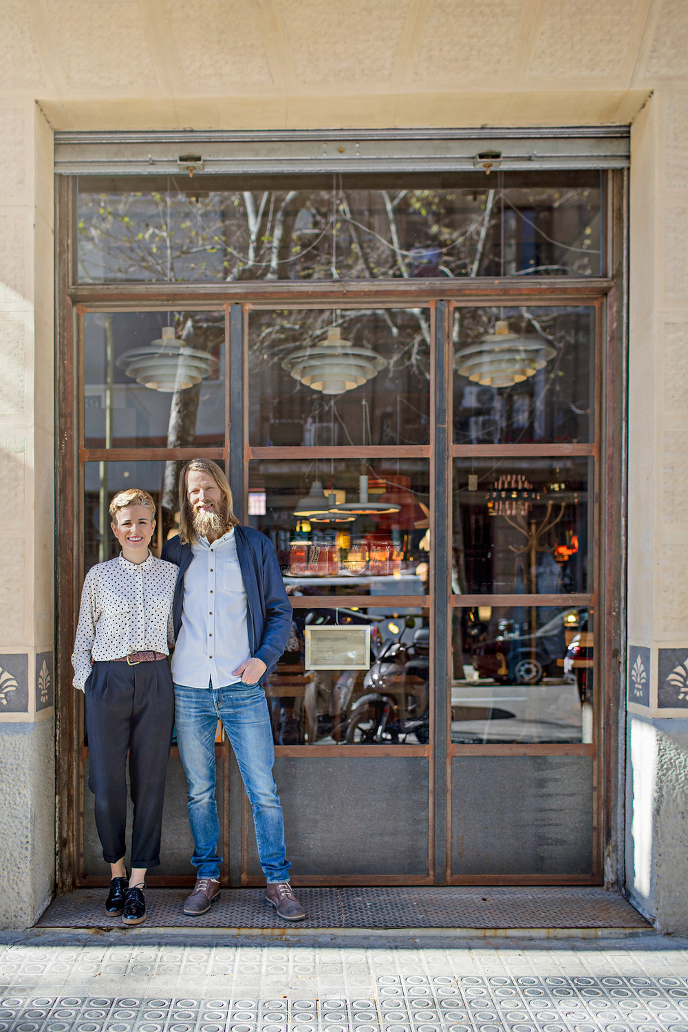 Photo of a young couple standing in front of their new small business.