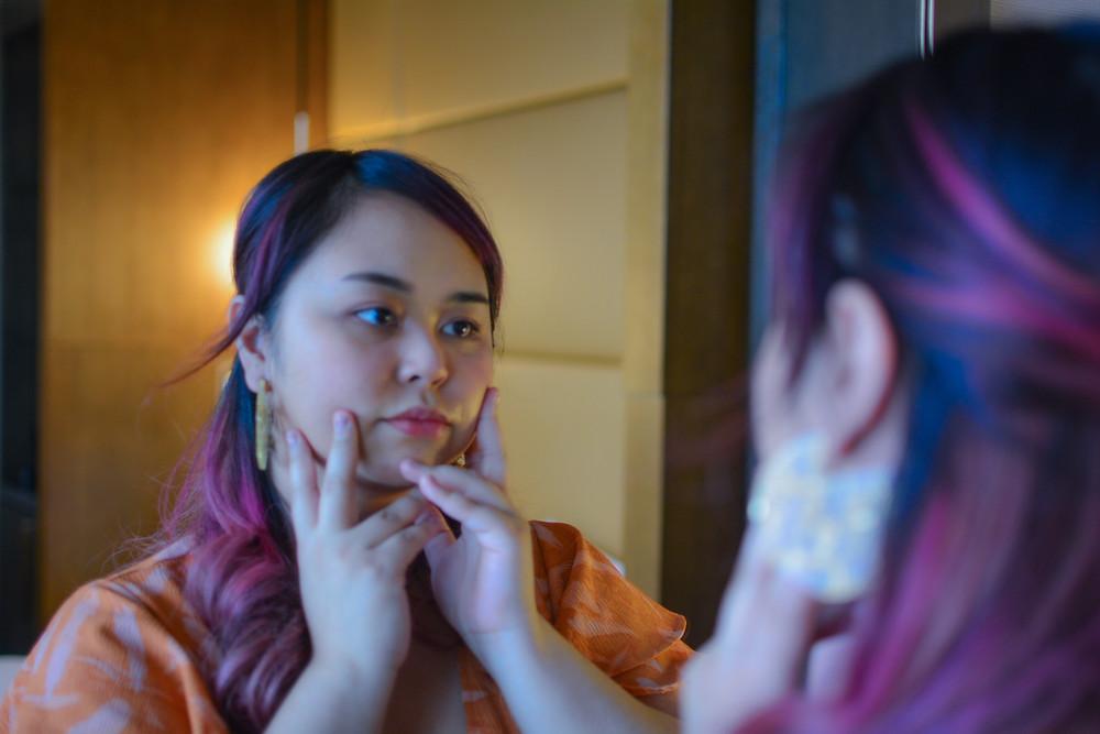 Shela looking at mirror self-care plan reflection