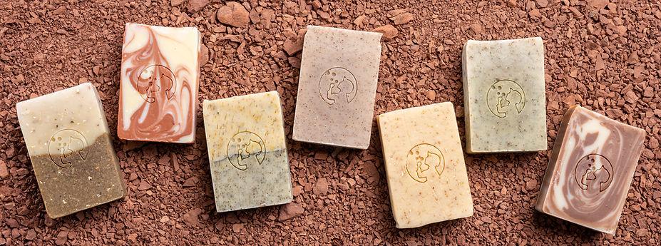 Savonnerie artisanale de l'Aveyron présente ses savons préambulle posés sur la terre du Rougier de Camarès, il y a sept savons différents saponifiés à froid, aux plantes sauvages de l'Aveyron comme l'ortie, le plantain et le pissenlit, au miel de l'Aveyron, au Chanvre, à l'amande douce, à l'argile rouge, au cacao...