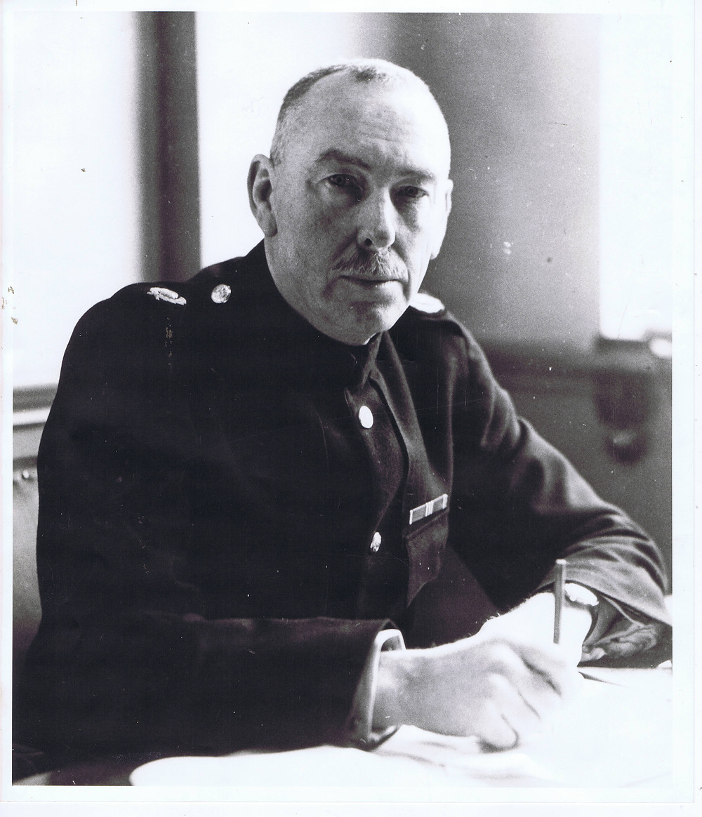 Chief Inspector McWalter sitting at his desk