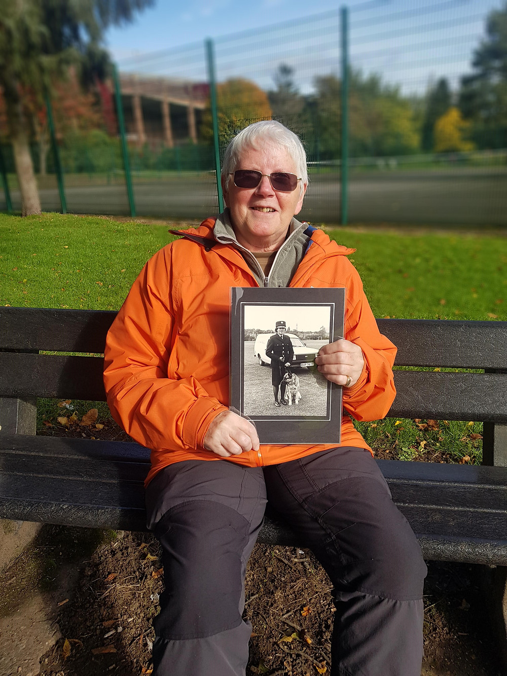 Jean sits on a bench holding a photograph of herself as a Birmingham Parks Police dog handler