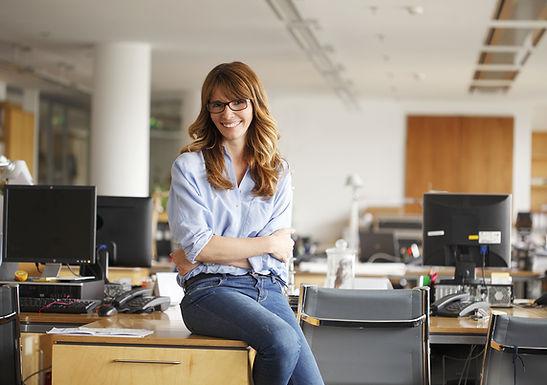Frau sitzt auf dem Schreibtisch