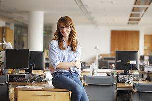 Mujer que se sienta en el escritorio
