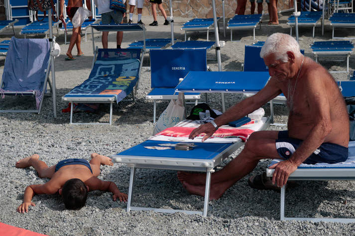 An older man presumably wins a game of cards against a young child who is not taking it well in Cinque Terra, Italy