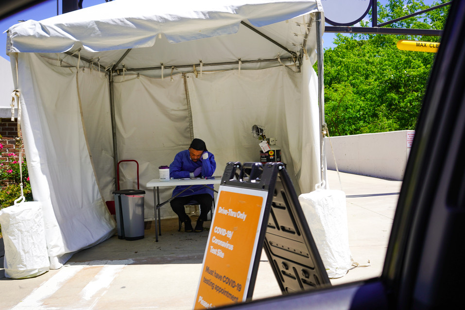 A man working the check in counter at a Covid testing site.