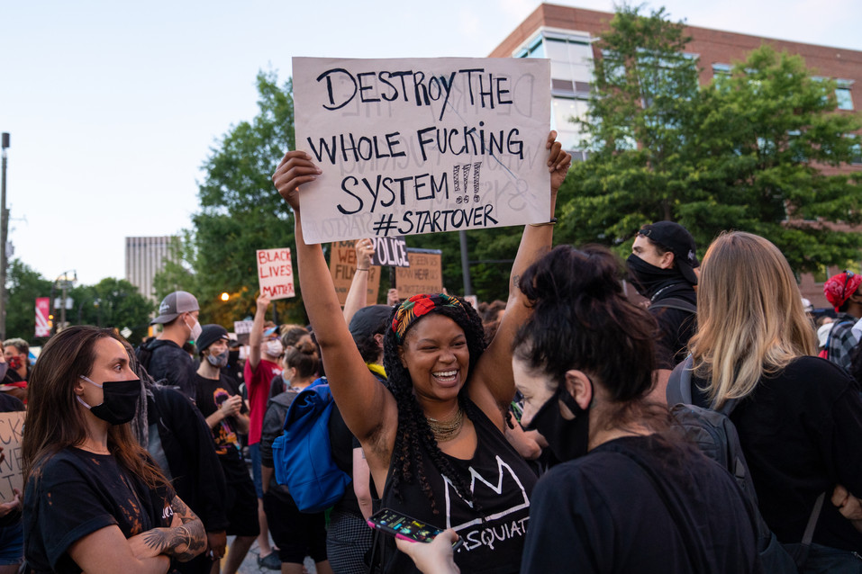 "A protestor holding a sign that reads ""Destroy the whole fucking system, #startover"""