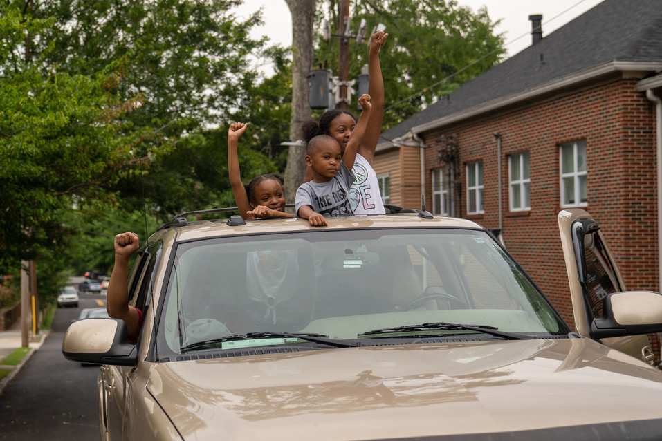 Children stand out of their sunroof supporting a march passing by their families car