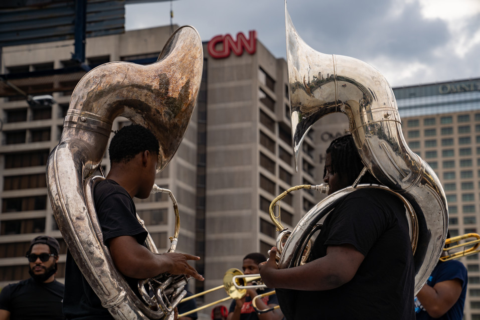 Part of a large brass band playing music and bringing positive energy to the third day of protests in Atlanta