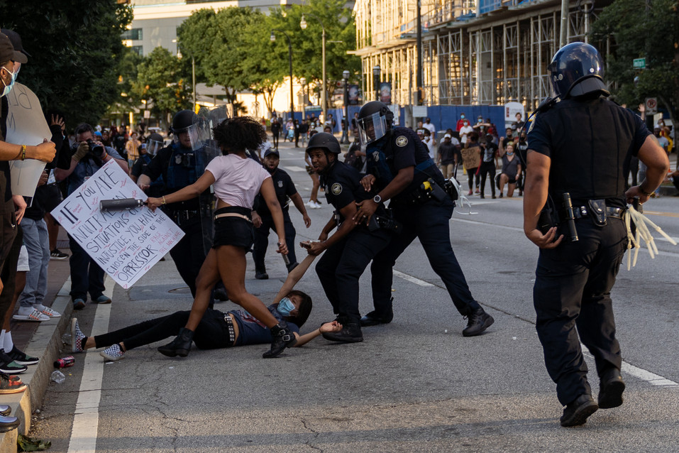 A female protester is being taken away by officers as her friend runs to help her May 31, 2020