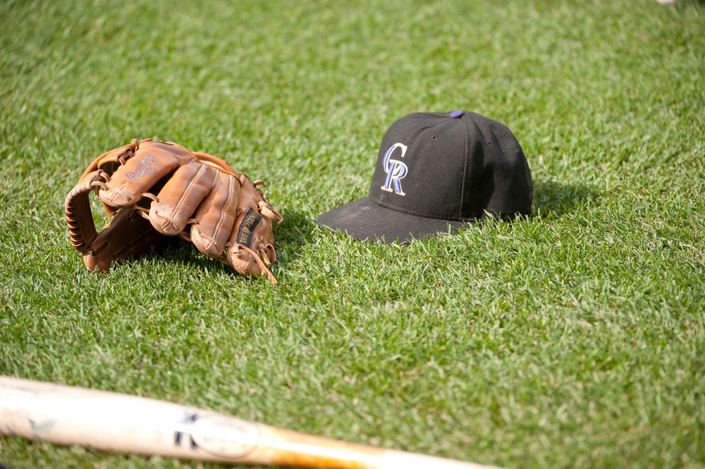 colorado rockies baseball cap glove and bat on field