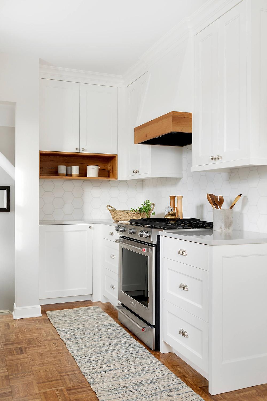 White oak kitchen hood mantel, white cabinetry.