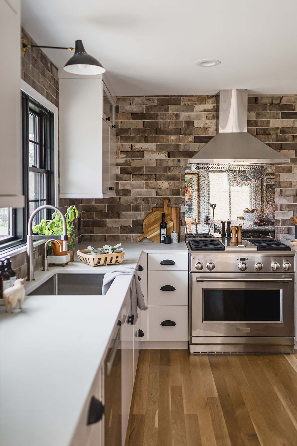 Contemporary industrial black and white kitchen with brick porcelain tile backsplash, custom cabinetry, stainless steel appliances, exposed range hood and antique mirror backsplash