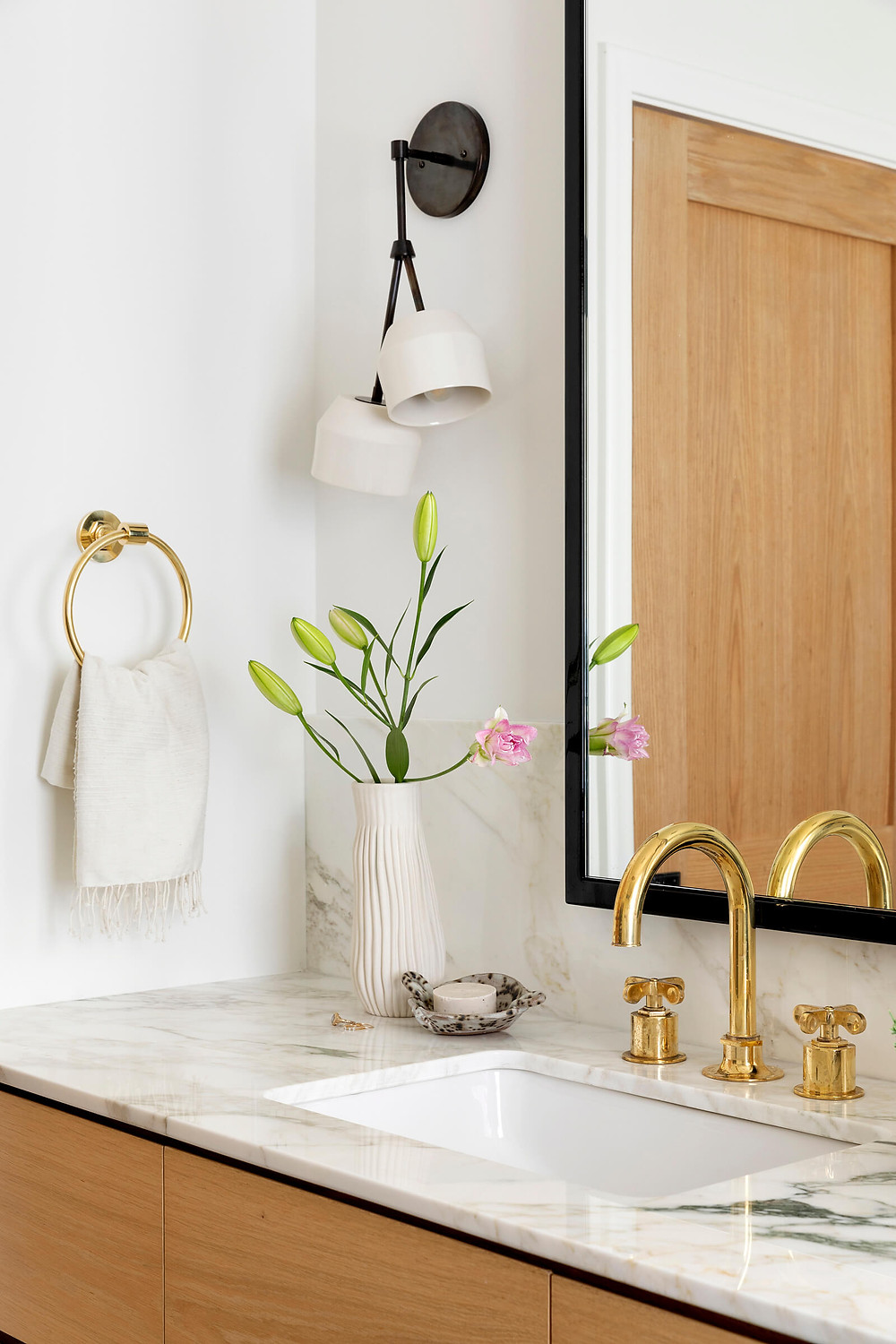 Modern bathroom white oak vanity with burnished brass Waterworks plumbing fixtures, marble countertop with extra tall backsplash and asymmetrical sconces
