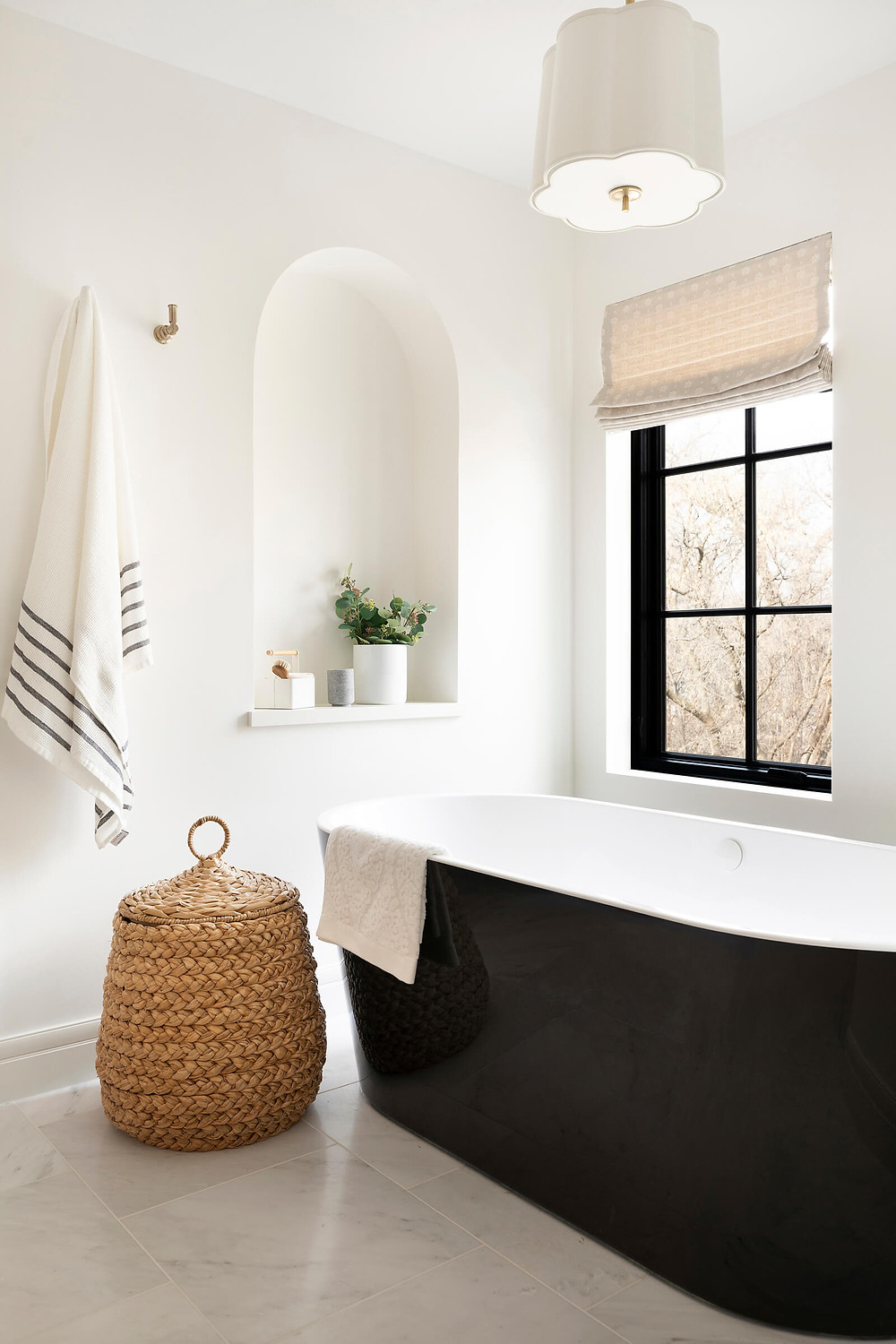 Owner's bathroom with arched niche detail, black freestanding bathtub and white marble tile floor.