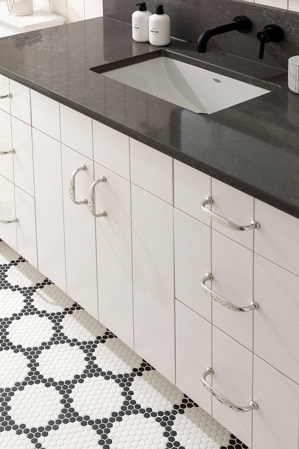 Benjamin Moore Cloudy Gray painted v groove vanity, black and white glass floor tile and black quartz countertop.