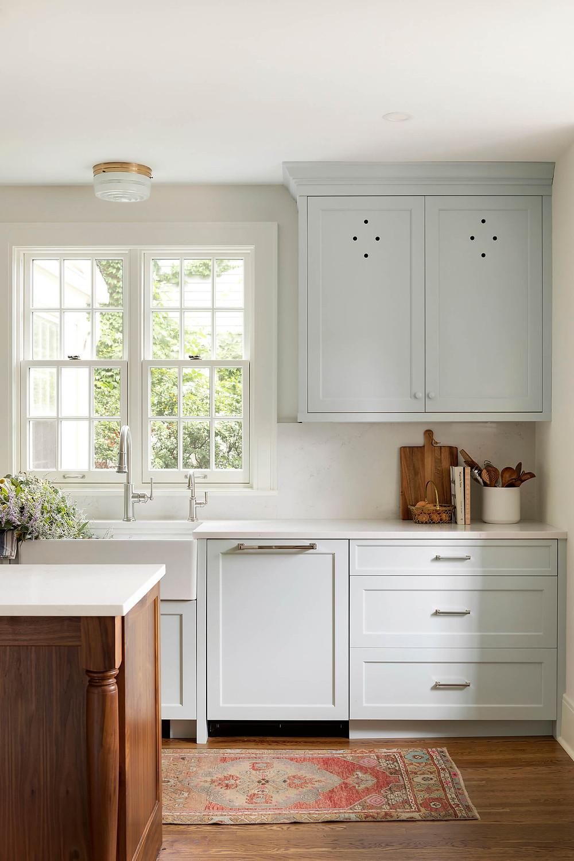 Custom blue cabinetry with larder vent hole detail, integrated paneled dishwasher, apron front sink, walnut island with custom leg