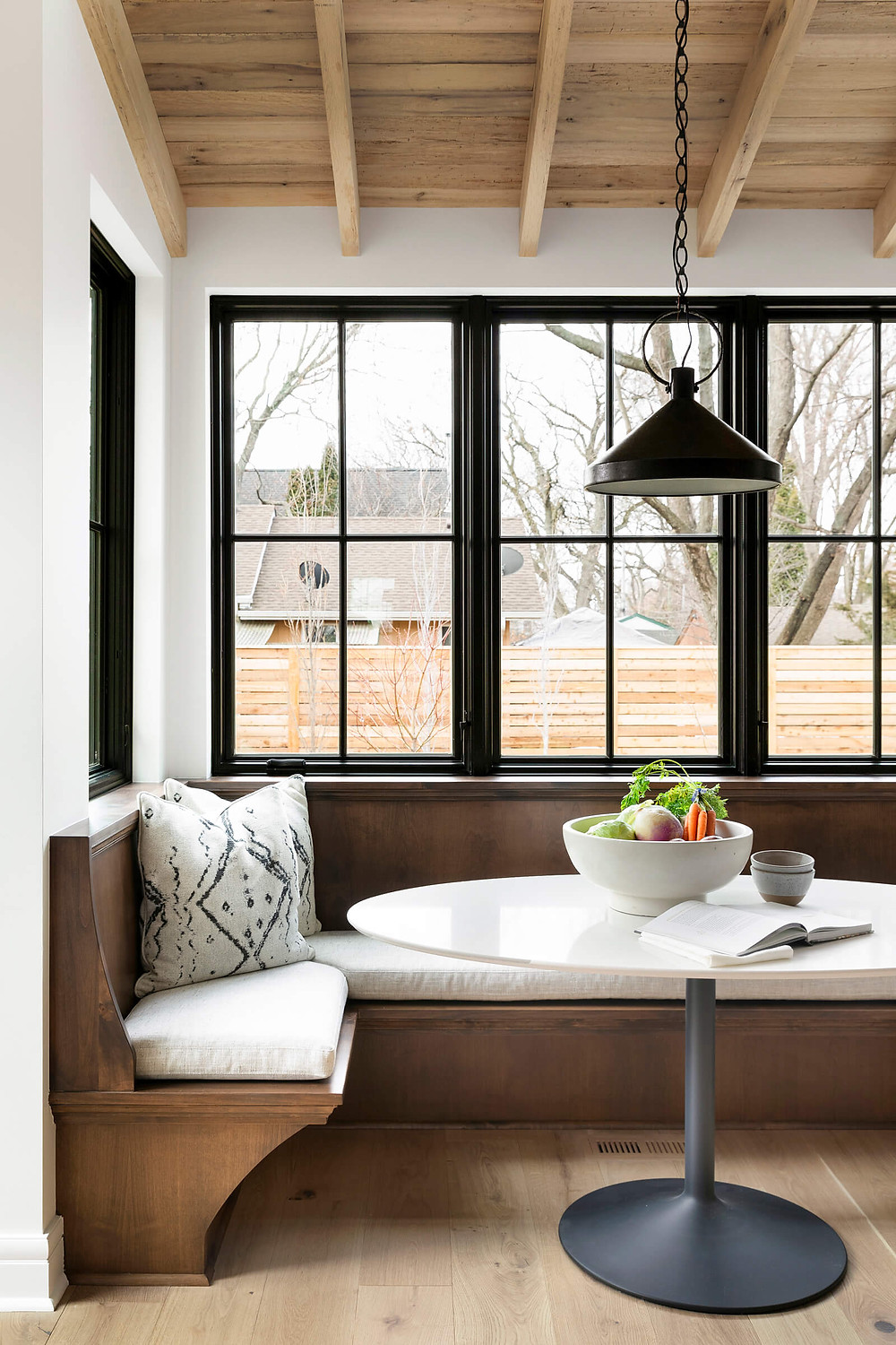 Custom breakfast dining nook banquette with reclaimed wood ceiling detail and large black grid windows