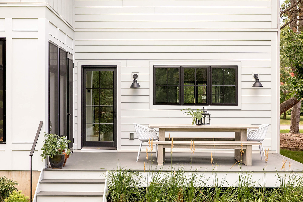 Outdoor patio with large black grill doors and windows with white Hardy siding