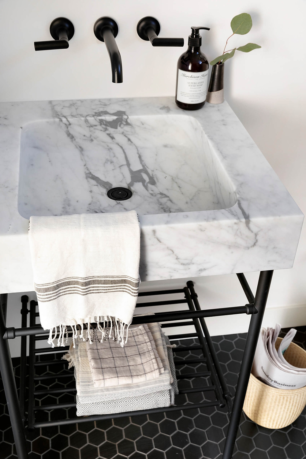 Custom marble console vanity top with black legs over black hexagon floor tile and Delta Trinsic wall mount faucet