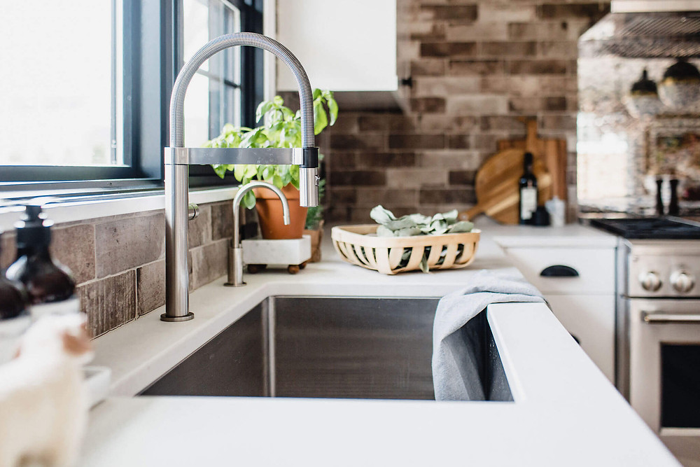 Contemporary industrial kitchen sink with articulating faucet and undermount stainless steel sink and quartz countertop