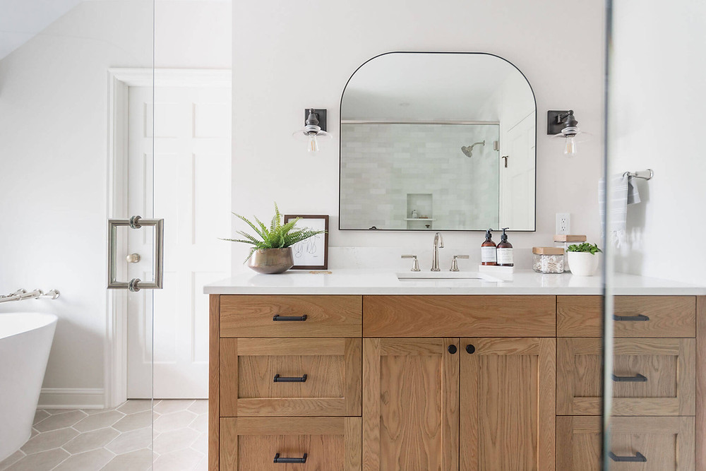 Primary owners suite bathroom custom stain white oak vanity with single sink, large mirror and industrial inspired sconces. Ivory hexagon floor tile and black accents