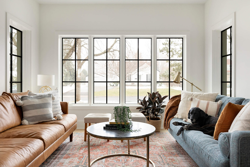 Modern traditional living room with black grid windows, white walls and vintage rug