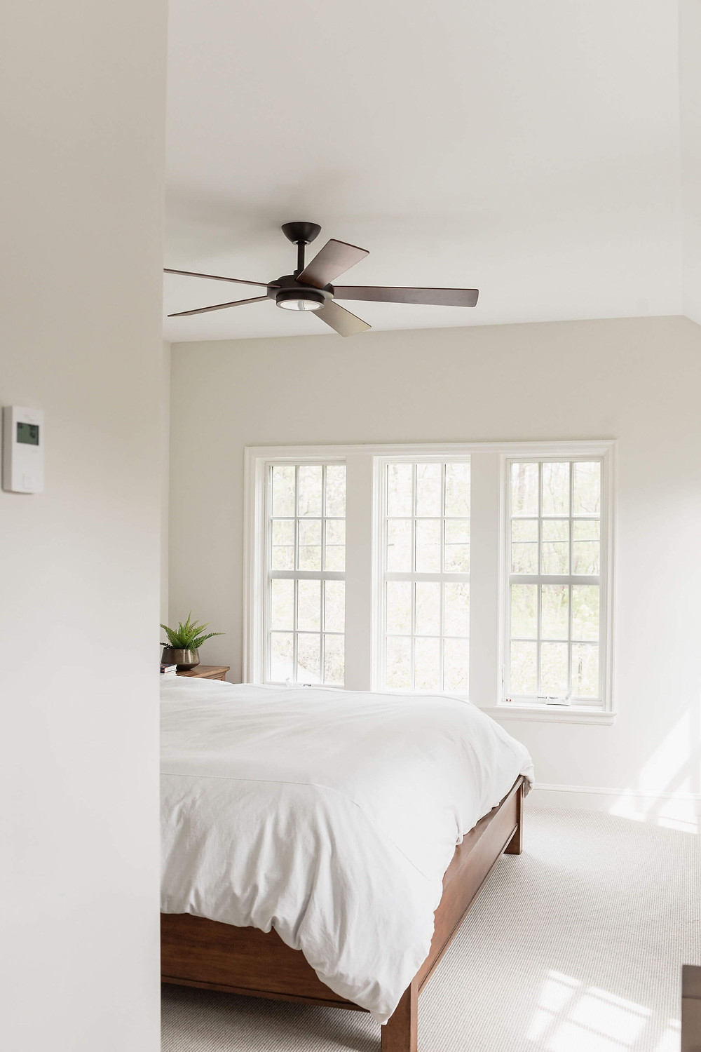 Light and bright primary owner's bedroom with large windows and modern farmhouse ceiling fan
