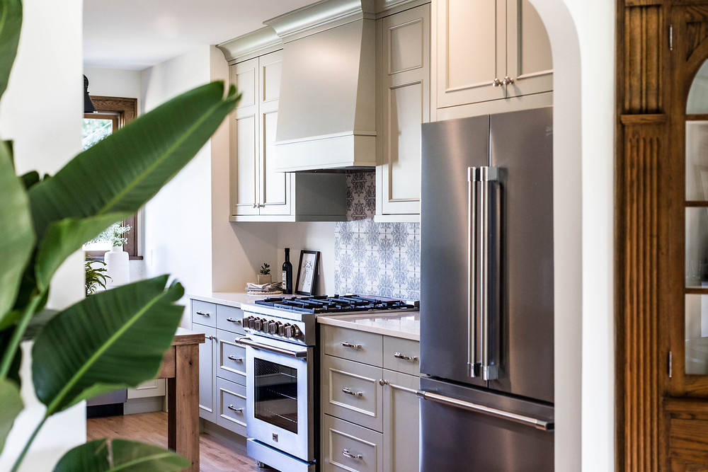 Beautiful custom cabinets with integrated range hood in soft green