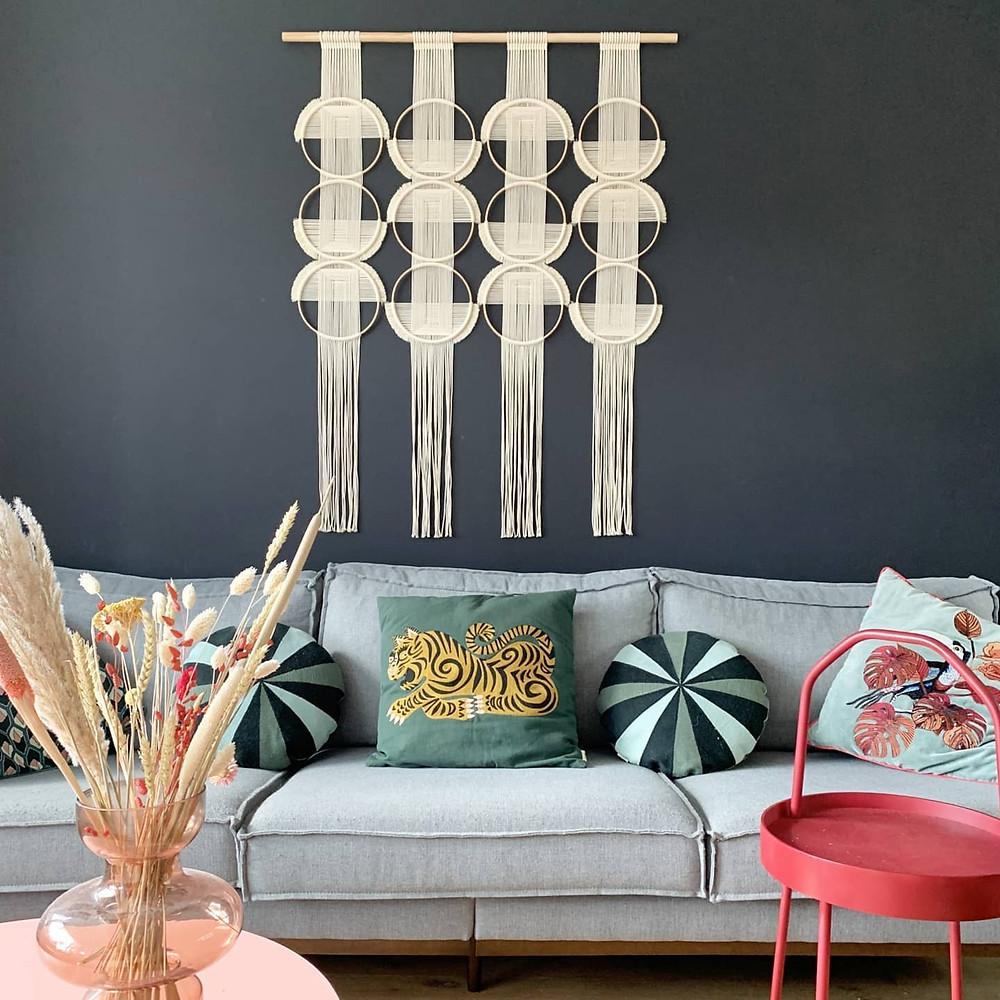 studio nom circle fiber art hung over living room sofa with colorful throw pillows