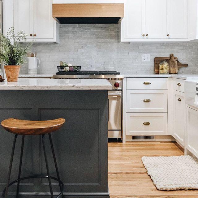White perimeter custom cabinetry with dark grey island, handmade artisan backsplash tile and soft white oak range hood mantel