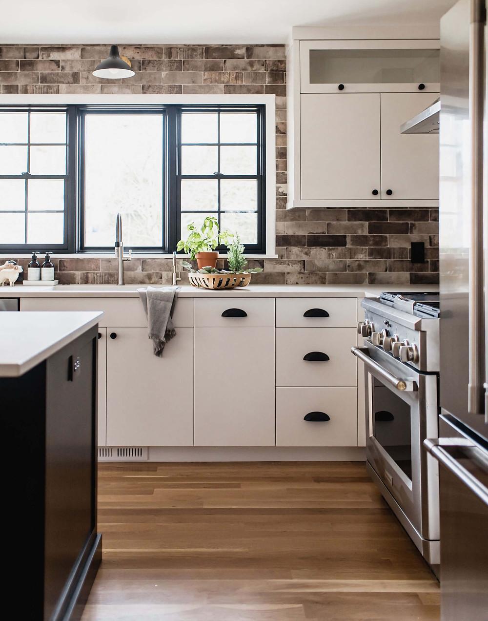 City industrial inspired kitchen with porcelain tile brick backsplash, black windows, white perimeter cabinets and black island