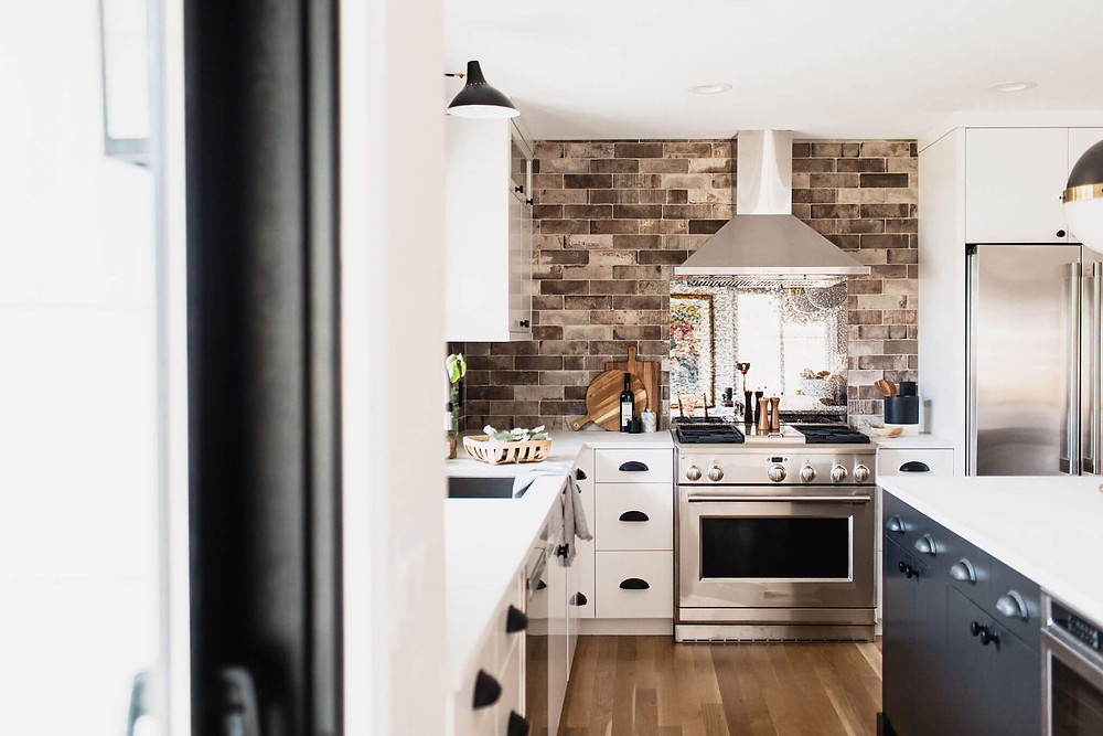 White and black contemporary industrial kitchen with brick tile backsplash and antique mirror range backsplash, exposed range hood