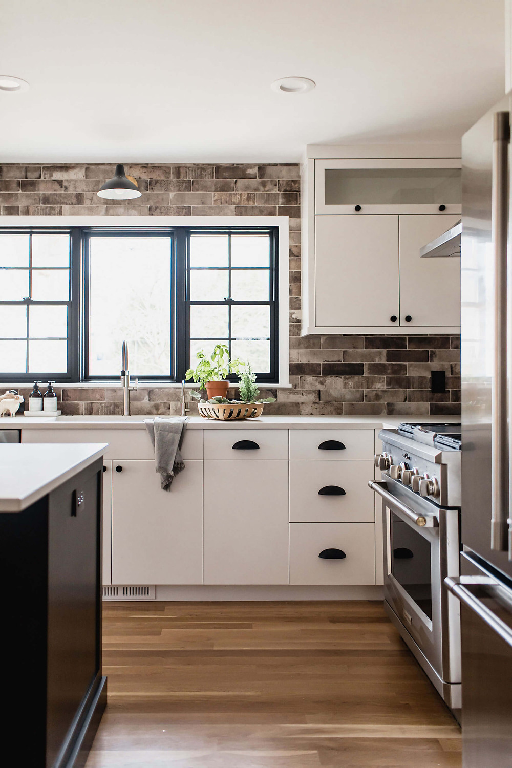 Industrial city inspired kitchen with porcelain brick backsplash to the ceiling and modern flat front cabinets with a large black window