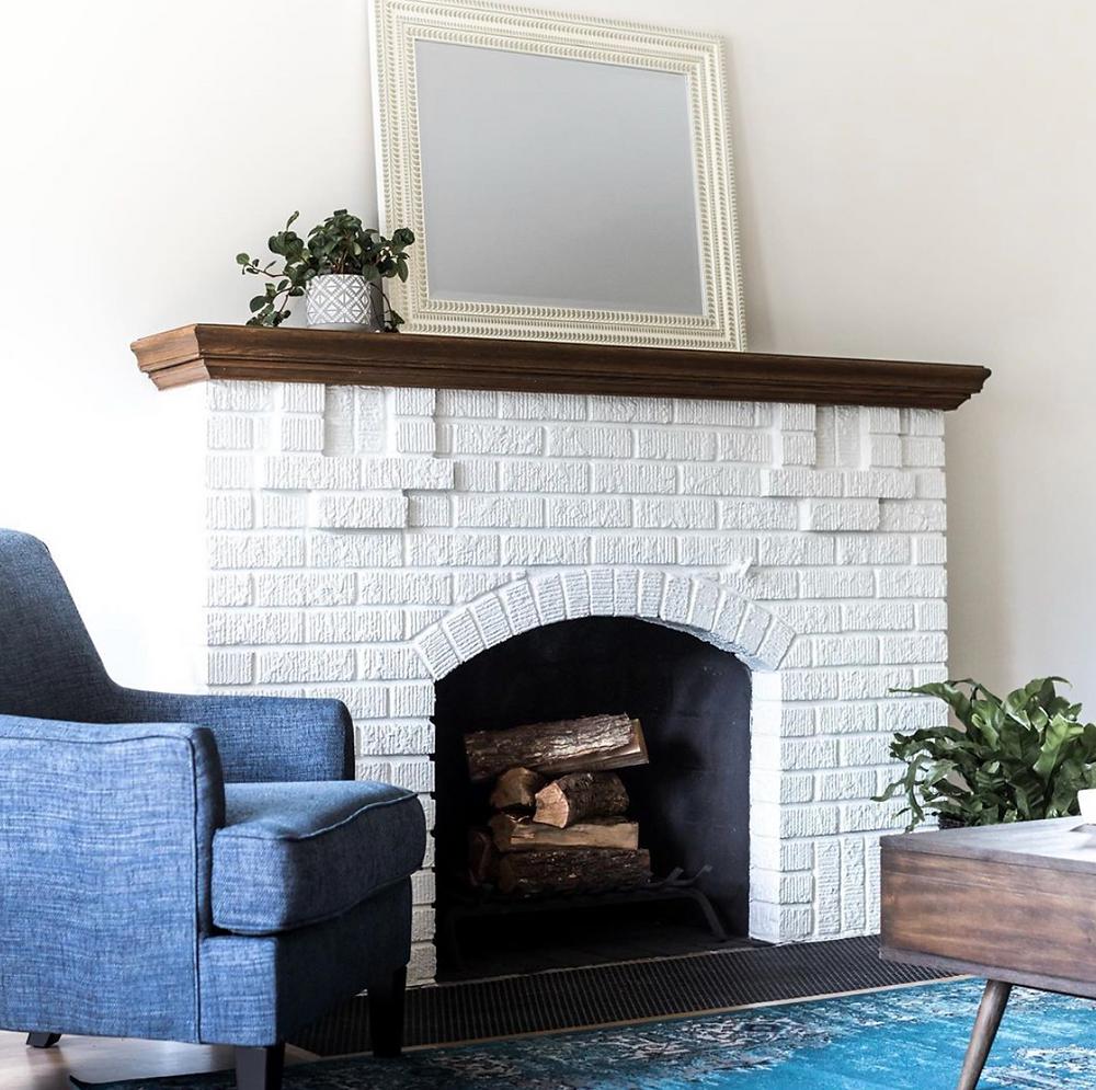 Beautiful oak vanity mantel over white brick fireplace at tudor home