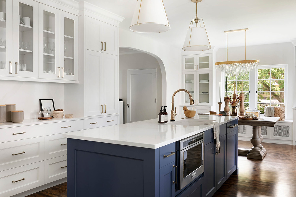 Charming white glass cabinet doors and blue island in kitchen renovation with modern lighting