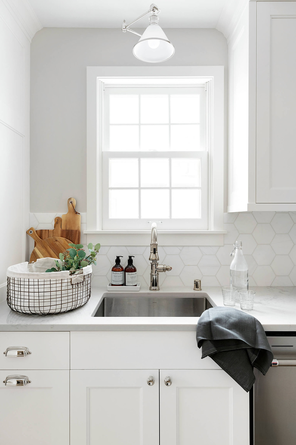 Kitchen sink, polished nickel faucet and lighting, white painted cabinetry.