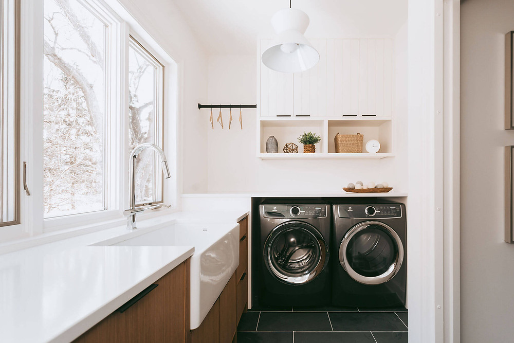 Scandinavian designed laundry room mudroom with custom rift white oak cabinetry, large apron sink, slate tile floor and white quartz countertop