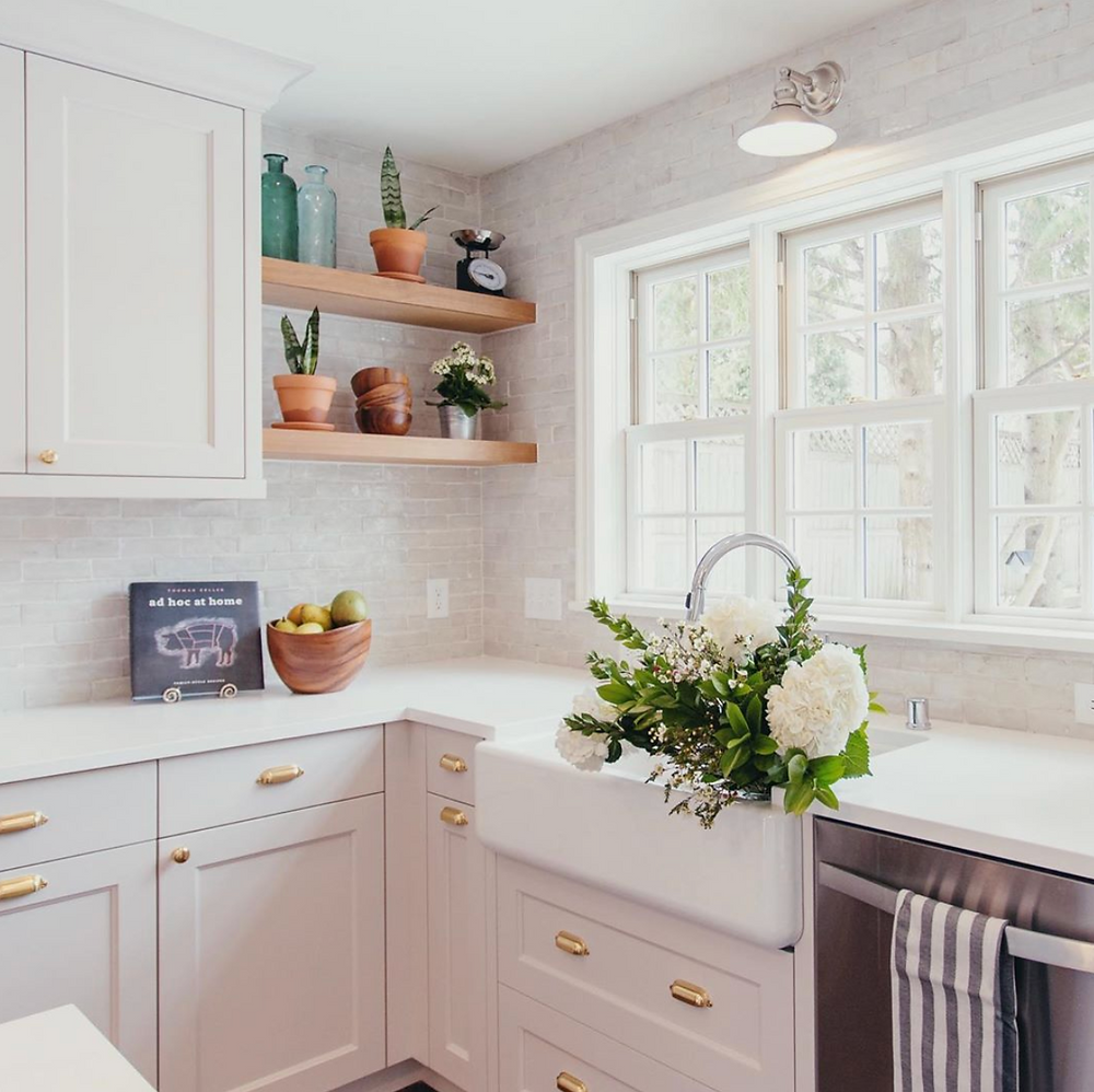 White kitchen artisan tile open shelving farmhouse sink brass hardware