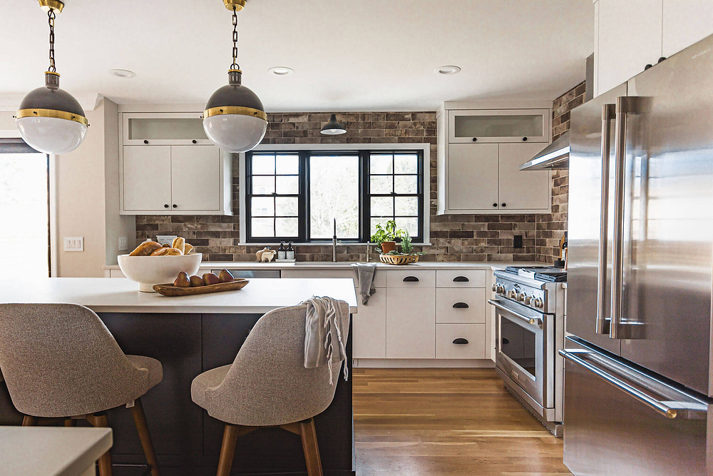 Large black window with grilles pair with industrial inspired kitchen with custom cabinets, mixed metal island pendants