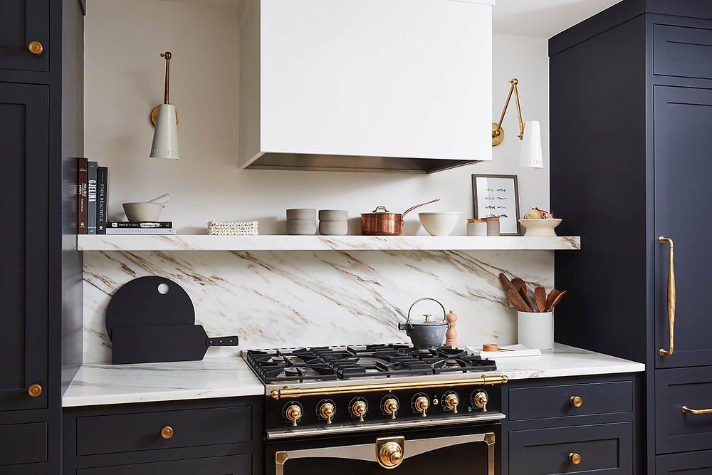 Custom kitchen cabinetry with dark moody blue inset cabinets, marble countertop and floating shelf and French inspired range